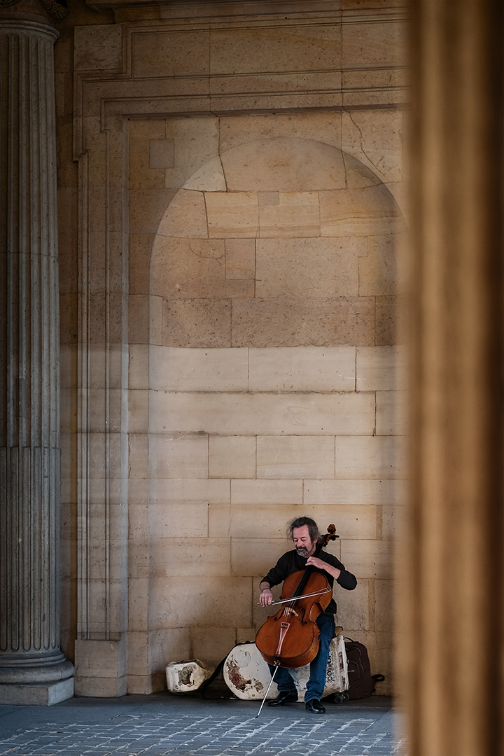 Photograph of a musician playing at the Louvre Art Museum in Paris France